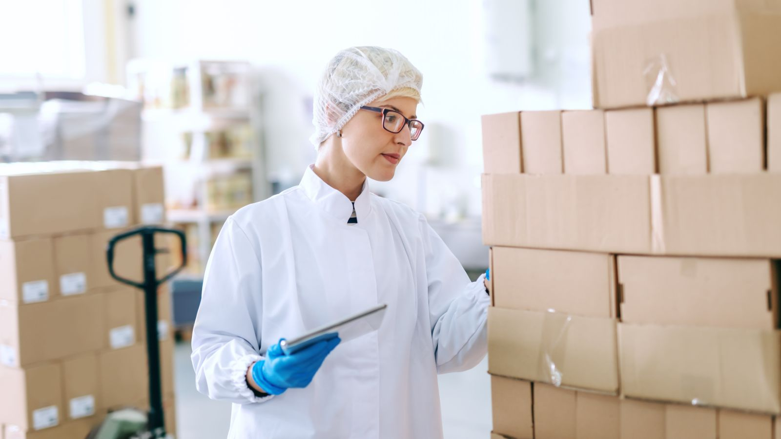 Worker quality checking boxes of stock