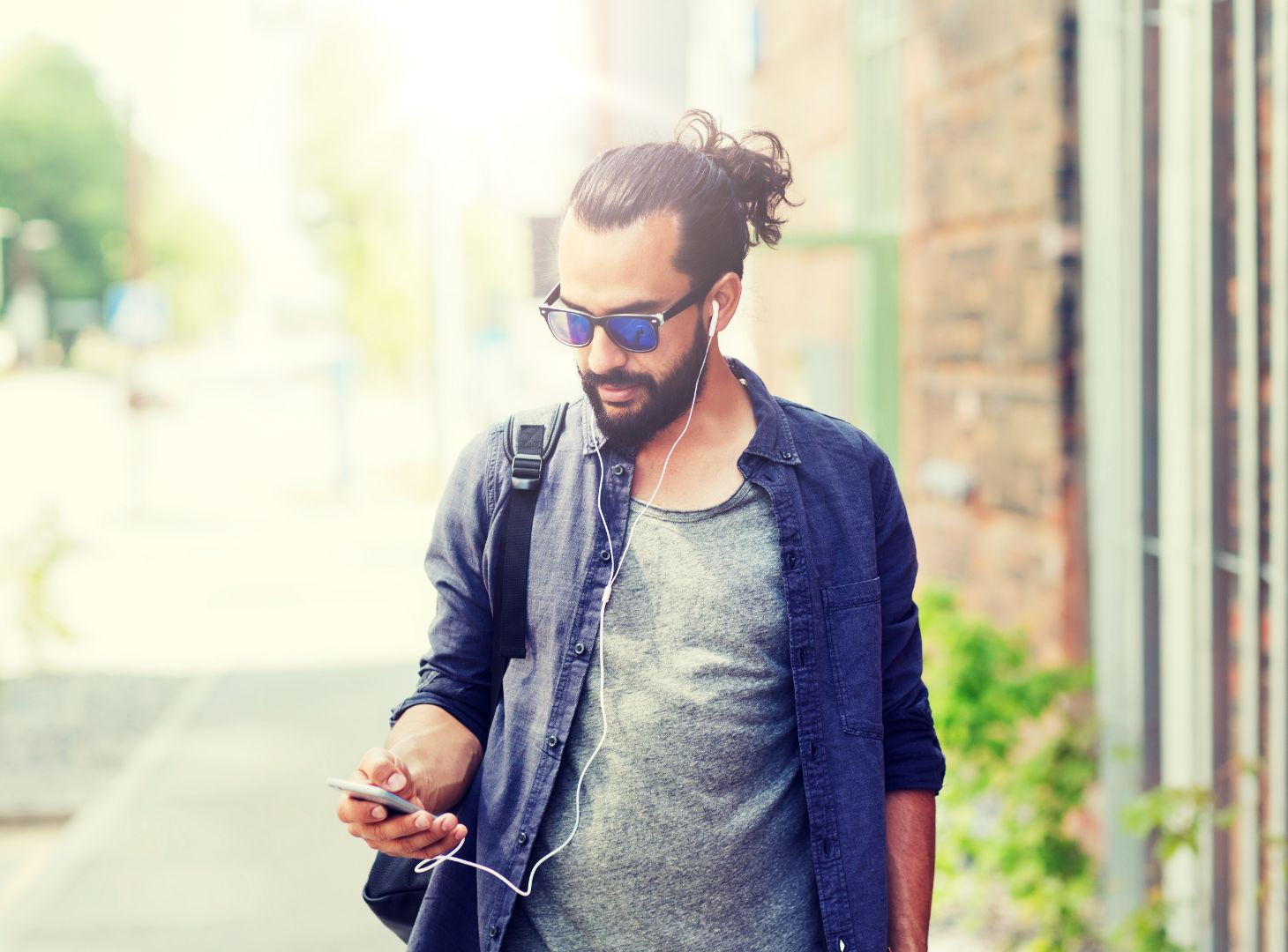 Image of man walking down road listening to a podcast