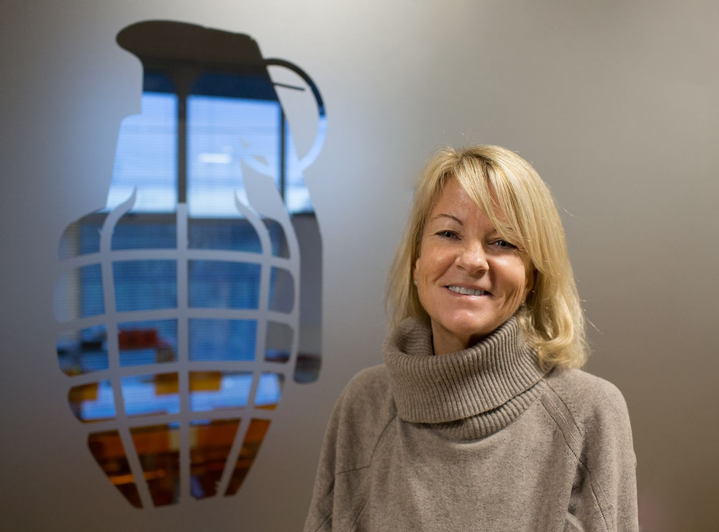 Image of Juliet Barratt, Co-Founder of Grenade stood next to Grenade Logo
