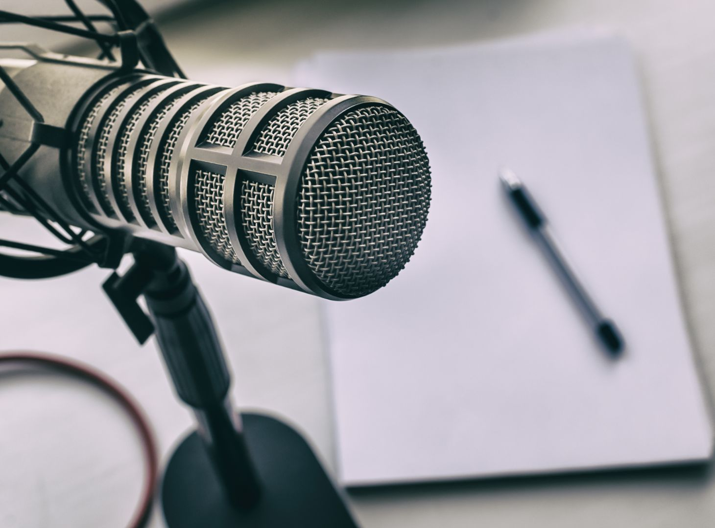 Image of a microphone on a table next to a pen and paper