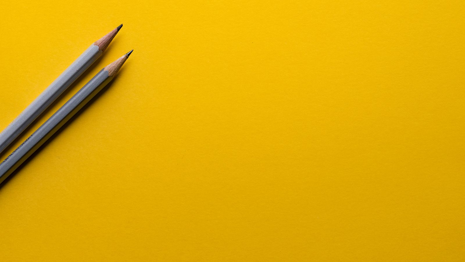 Image of 2 pencils on a yellow background