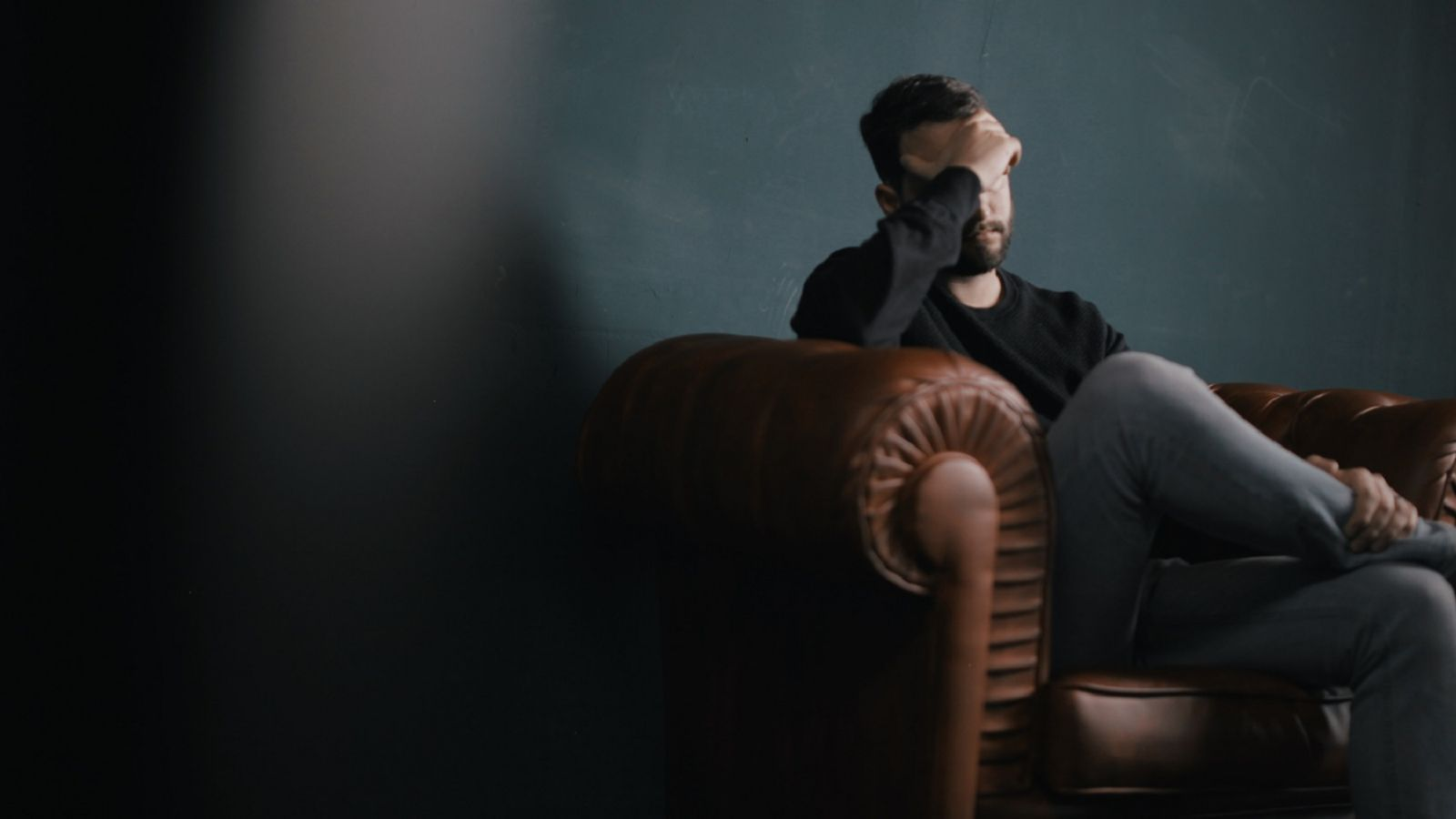 Man sat on brown leather sofa resting head in hands