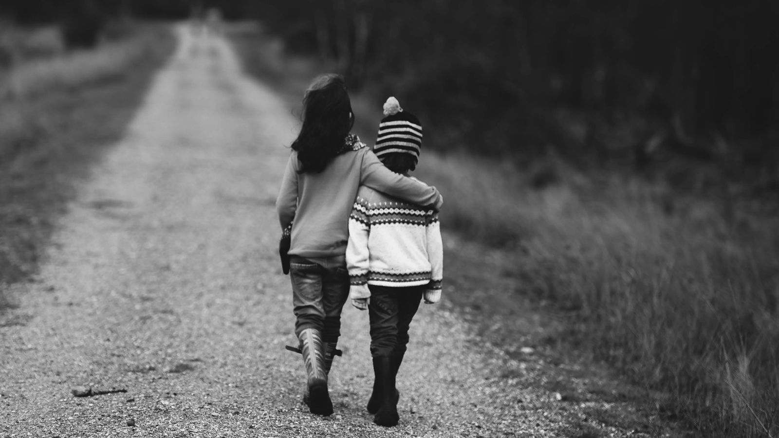 Image of boy and girl walking along a path with arms around each other